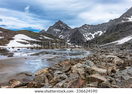 Rocks, water and alluvial sand in a small mountain valley formed by glacial erosion. Tunka range - stock photo