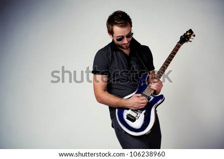 Rockstar playing on guitar. Wearing sunglasses - stock photo