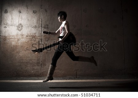 Rockstar running with her guitar outdoors in night. - stock photo