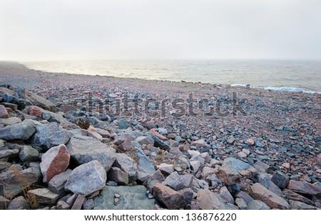 Rocky Baltic sea shoreline in the cold mist - stock photo