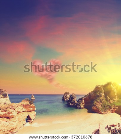 Rocky beach at sunset  with cloud in form of heart , Lagos, Portugal. Counter light.  Business, Love and travel concept - stock photo