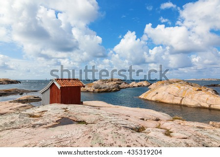 Rocky beach by the sea and a shed - stock photo