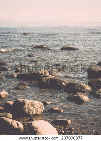 rocky beach in the baltic sea with plants and skyline - retro, vintage style look