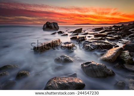 Rocky beach long exposure seascape at sunrise - stock photo