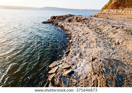 Rocky beach of great lake in sunset