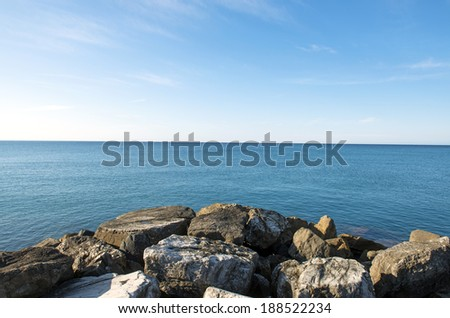 Rocky beach with blue sea, and blue sky. - stock photo