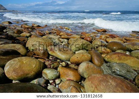 Rocky beach with large smooth pebbles and waves on a sunny morning
