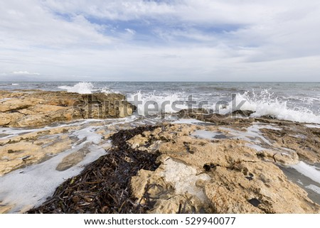 Rocky beach with waves in Santa Pola, Alicante province, Spain.