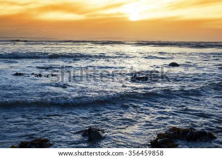 rocky beal beach near ballybunion on the wild atlantic way ireland with a beautiful yellow sunset - stock photo