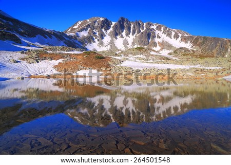 Rocky bottom of a lake and distant summits mirrored by calm lake - stock photo