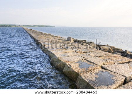 Rocky breakwater jetty extends for seven-eighths of a mile from shore to middle of bay in Rockland, Maine