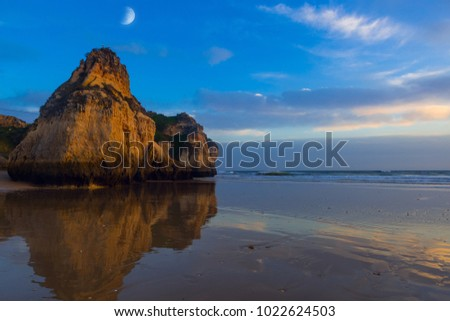 Rocky cliffs reflected on wet sandy beach at Beach of the Three Brothers near Portimao, Portugal.