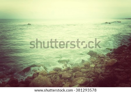 Rocky coast and stormy sea in green glow. Retro style photo. - stock photo