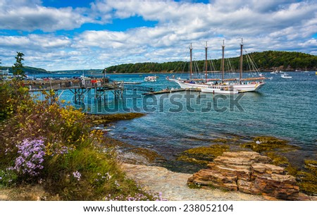 Rocky coast and view of boats in the harbor at Bar Harbor, Maine. - stock photo