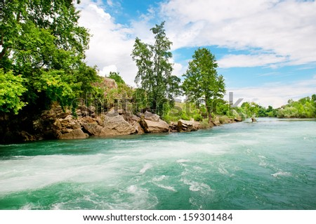 rocky coast river and the blue sky - stock photo
