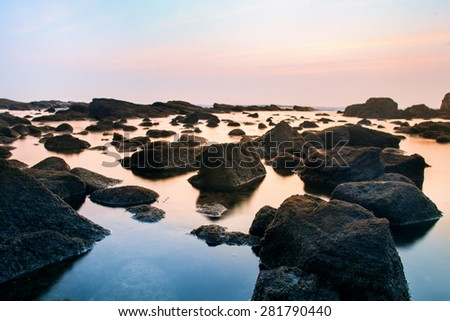Rocky coast with beautifully coloured clouds at sunset. - stock photo