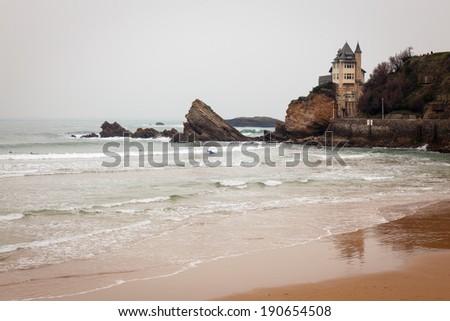 Rocky coastal beach seascape in Biarrtiz, France on the Atlantic ocean. Surfers in the water surfing green waves towards a sandy beach. / Seascape in Biarrtiz, France. - stock photo