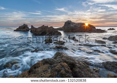 Rocky coastal sunset seascape with sunburst. This seascape was taken at sunset with sunburst peeking through the rocks.  This photo was taken at Corona del Mar, Newport Beach, California. - stock photo