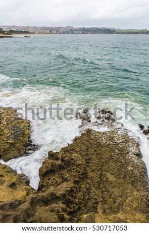 Rocky coastline along cliffs with the Sardinero beach in the background in Santander, Cantabria, Spain