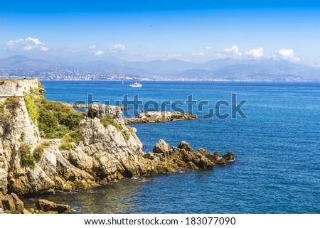 Rocky coastline on the Mediterranean Sea of Antibes. Antibes is a resort town in the Alps-Maritimes department in southeastern France between Cannes and Nice, Cote d'Azur. - stock photo