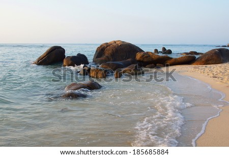 rocky coastline with a little sandy beach and big boulders - stock photo