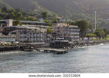 Rocky coastline with hills, pier and a hotel in Roseau, on Caribbean island Dominica. - stock photo