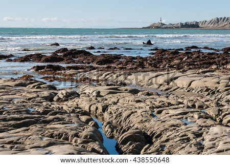 rocky coastline with lighthouse in distance - stock photo