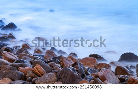 Rocky coastline with misty water.  Shot as a Long exposure - stock photo