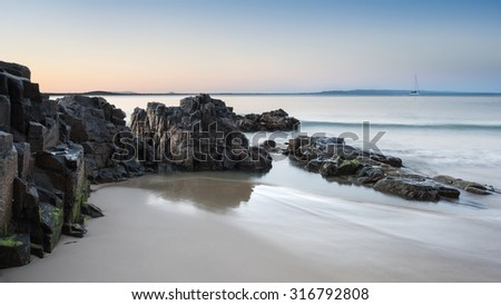 Rocky Coastline With Sand, Clear Sky, Calm Ocean and a White Sail Boat During a Peaceful Sunset, Little Cove, Noosa National Park, Noosa Heads, Sunshine Coast, Australia - stock photo