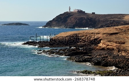 Rocky coves and lighthouse, tip of Arinaga, Gran canaria, Canary islands  - stock photo