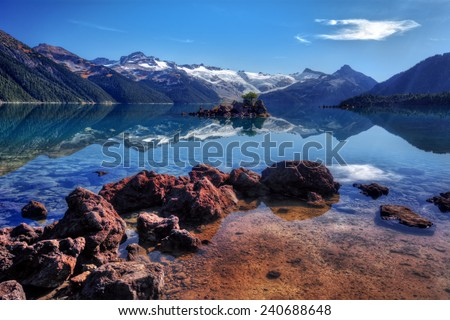 Rocky formation by a lake with distant mountains and an isolated tree on a rocky isle - stock photo