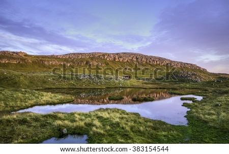 Rocky hill reflecting in a Small Lake at Sunset with Blue Sky and Overcast Clouds (Faroe islands)