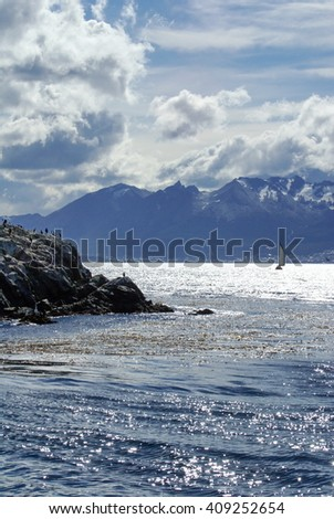 Rocky island in the Beagle Channel, off the Straight of Magellan, with snow covered mountains in the distance and a sailboat passing behind it, near Ushuaia, Argentina - stock photo