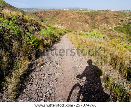 Rocky landscape and silhouette of cyclist. Tenerife. Canary Islands. Spain - stock photo