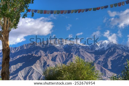 stock-photo-rocky-landscape-of-with-ice-peaks-in-background-blue-sky-and-fluffy-clouds-ladakh-jammu-and-252676954.jpg