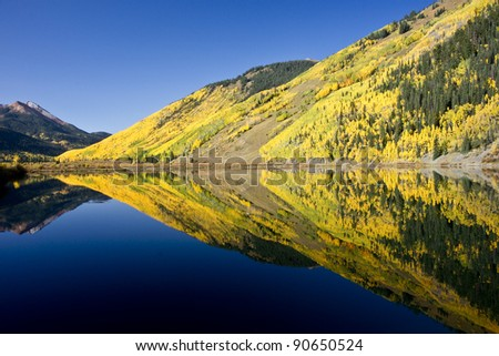 Rocky Mountain foliage reflects in a clear mountain lake - stock photo