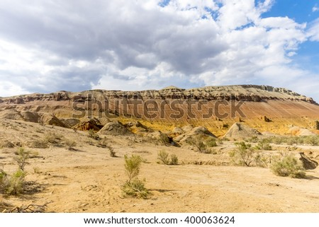 rocky mountain in the desert under cloudy sky - stock photo