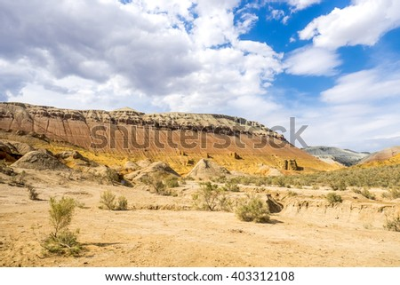 rocky mountain in the desert under cloudy sky