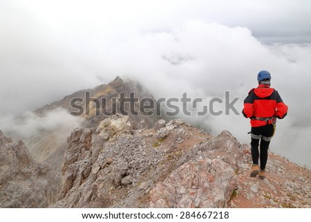 Rocky mountain ridge and isolated climber walking above the clouds, Dolomite Alps, Italy - stock photo
