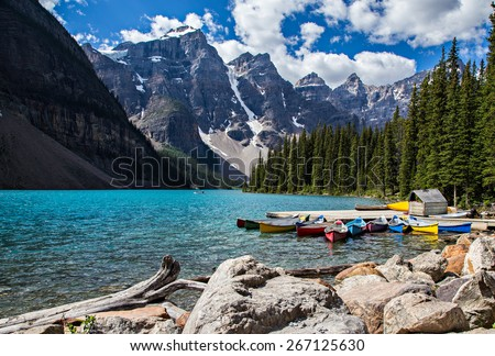 Rocky Mountain view at Moraine Lake in Banff National Park. Blue glacial water and fir trees with canoes.   - stock photo