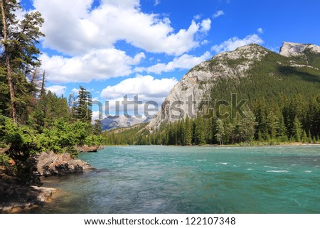 Rocky mountains covered with coniferous forest and Bow river flowing in a valley between mountains in Banff National Park (Alberta, Canada) - stock photo