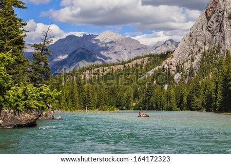 Rocky mountains covered with coniferous forest and Bow river flowing in a valley between mountains in Banff National Park (Alberta, Canada)