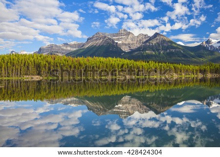 Rocky mountains lake landscape. Herbert Lake with reflection of cloudy sky. Banff National Park, Alberta, Canada