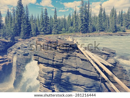 Rocky mountains landscape with Athabasca River flowing in Jasper National Park. (Alberta, Canada). Image done in vintage retro instagram style - stock photo