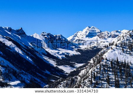 Rocky Mountains Maroon Bells.  The Rocky Mountains of Colorado, with the Maroon Bells Peak, as viewed from the top of the Aspen Snowmass ski resort on a clear winter day.  - stock photo