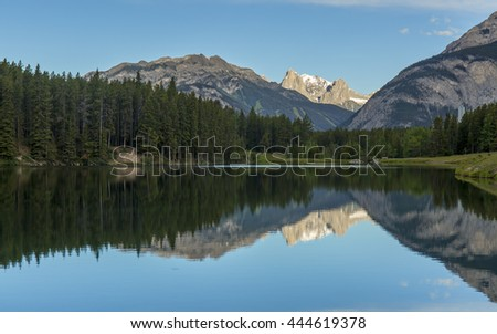 Rocky Mountains reflect in Johnson Lake - Banff National Park, Alberta, Canada - stock photo