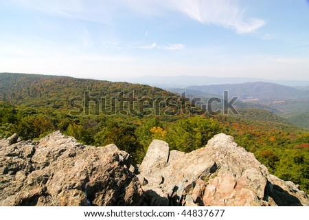 rocky mountian peak and view of an autumn valley
