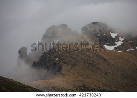 Rocky peak covered in clouds - stock photo