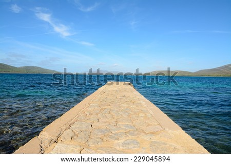 rocky pier in Porto Conte under a blue sky with small clouds - stock photo