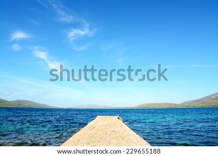 rocky pier under soft clouds. Shot in Porto Conte, Sardinia. - stock photo